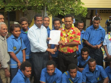 (in floral shirt) MP Daniel Mona presenting a cheque to Port Moresby Institute of Matriculation Studies.