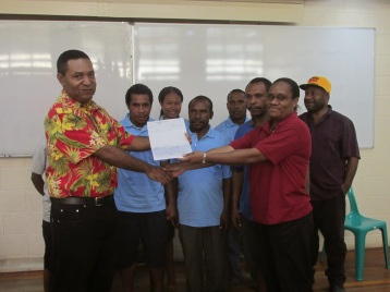 (floral shirt) Mona presenting cheque to UPNG accounts staff.