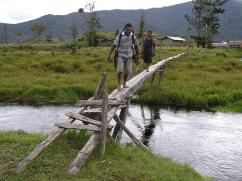 Escorts walkng a one lane foot bridge at Kosipe
