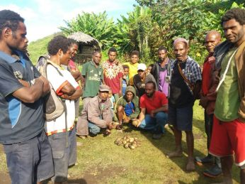 Michael Atuai with the Farmers after sample harvest at Kambisea